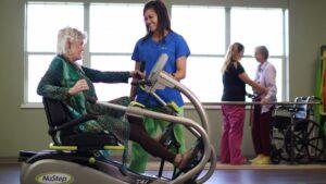 ER Senior Management   Resident exercising with associate's help