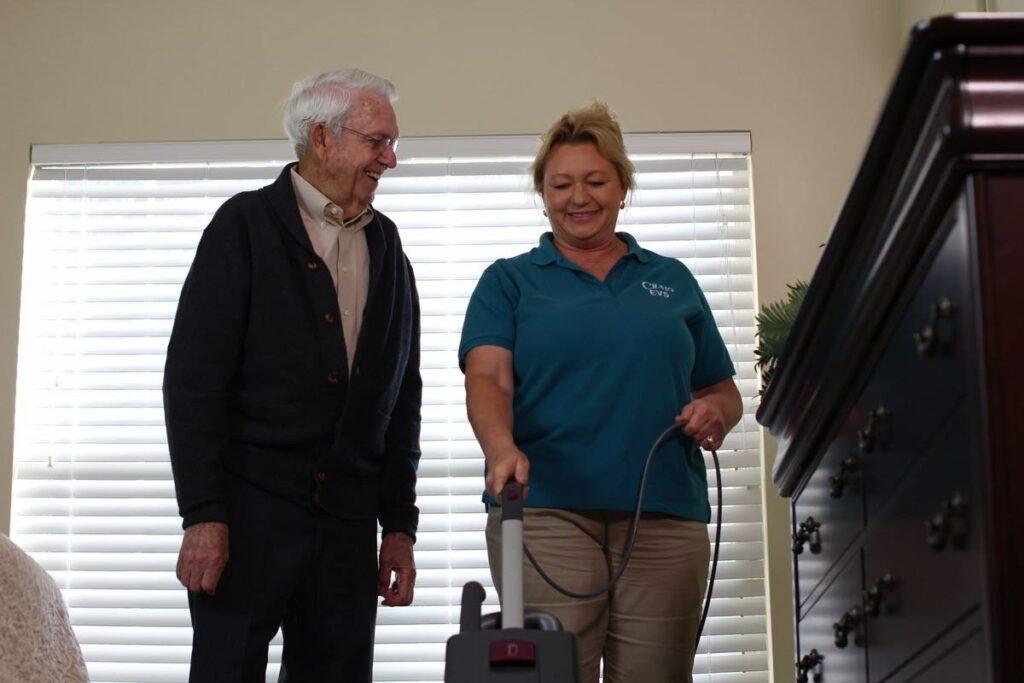 ER Senior Management | Associate vacuuming for resident