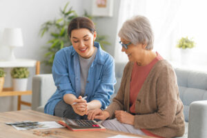 Evergreen Senior Living | Senior woman calculating financial information with associate