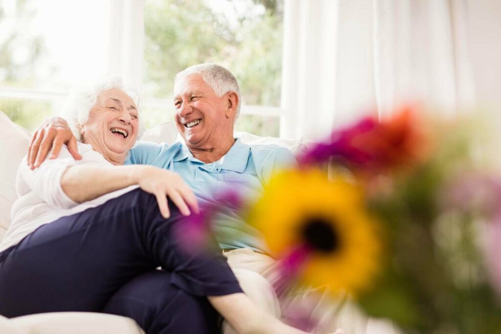 ER Senior Management   Senior couple on couch, laughing with flowers next to them